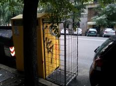 Un raccoglitore buttato accanto al cassonetto giallo